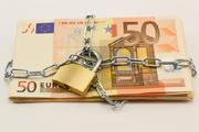 Geldstapel mit Kette und Schloss